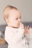 Otto mesi della neonata che porta la sua tettarella alla sua bocca Fotografia Stock