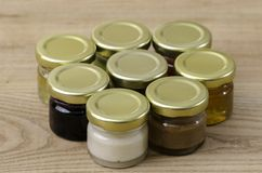 Otto piccoli barattoli di miele dei sapori dei differents Immagine Stock