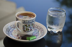Ottoman coffee presentation. Iznik tiles and Turkish coffee cup motif, besides cold water Stock Photo