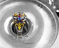 Ottoman vintage ring. Artistic hand made ring with ruby, sapphire, tourmaline & fleur de lys detail set in Ottoman style hammered silver and bronze over vintage Royalty Free Stock Photo