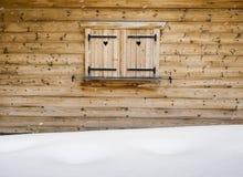 Otturatori di legno su una finestra di cabina con il cumulo di neve nel forground Immagini Stock