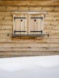 Otturatori di legno su una finestra di cabina con il cumulo di neve in priorità alta Fotografia Stock