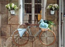 Otturatori di una casa nella città Antibes decorata piacevolmente con i vasi da fiori variopinti e la parete con una bicicletta immagine stock libera da diritti