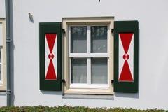 Otturatori sulle finestre olandesi con progettazione rossa e bianca tradizionale fotografia stock libera da diritti