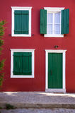 Otturatori verdi su una parete rossa Fotografia Stock