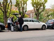 Otwarci bagażników ludzie stawia bagaż w wielkim bagażniku Fotografia Stock