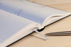 Otwarta agenda i pióro na drewnianym stole Obrazy Stock