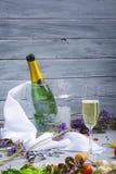 Otwarta butelka szampan w wiadrze z lodem, szkło szampan, srebny corkscrew na lekkim drewnianym tle Obraz Stock