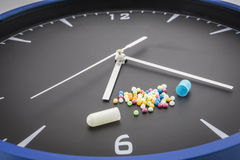 Otwarta czerwona kapsuły pigułka z balowym koloru lekiem na czerń zegarze Zdjęcia Stock