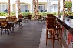 Otwarta kawiarnia z prętowym biurkiem z drewnianymi stołami i krzesłami na ulicie z otwartą werandą w tropikalnym ciepłym kraju fotografia stock