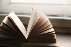 Otwarta książka na nadokiennym parapecie z ciepłym światłem, zdjęcia royalty free