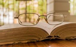 Otwarta książka na stole lub eyeglass na drewnianym stole na ciepłym pogodnym ranku i specs, boczny widok zamknięty w górę Niedzi zdjęcia stock