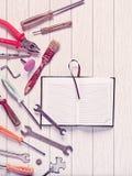 Otwarty dzienniczek z pustymi stronami i różnorodni narzędzia jesteśmy na białym drewnianym tle Zdjęcia Stock