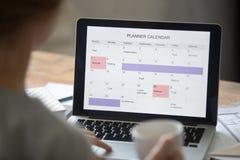 Otwarty laptop na biurku, planisty kalendarz na ekranie zdjęcia stock