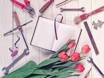 Otwarty notatnik z pustymi stronami, dzienniczek, bukiet czerwoni tulipany i różnorodni narzędzia lub, jesteśmy na białym drewnia Fotografia Stock