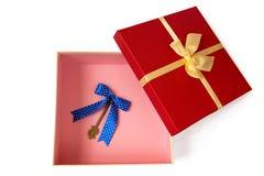 Otwarty prezenta pudełko z złocistym tasiemkowym łękiem i roczników klucze z błękitnym łękiem inside Zdjęcie Royalty Free