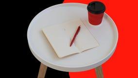 Otwarty pusty pusty nutowy papier z czerwonym pi?rem, czerwony kartonowy fili?anka kawy i?? na bia?ym round czasopisma drewna sto zdjęcie stock