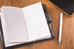 Otwarty rzemienny notatnik z białym piórem i telefoniczny kłamstwo na drewnianym stole obraz royalty free