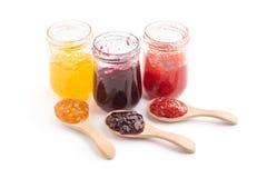 Otwarty słój truskawka, pomarańcze i czarne jagody, przyskrzyniamy i łyżka, odizolowywająca na bielu zdjęcie stock