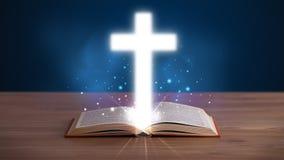 Otwiera świętą biblię z rozjarzonym krzyżem w środku Zdjęcia Stock
