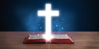 Otwiera świętą biblię z rozjarzonym krzyżem w środku Obrazy Royalty Free