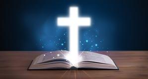 Otwiera świętą biblię z rozjarzonym krzyżem w środku Zdjęcie Stock