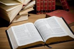 Otwiera biblię z stosem książki na tle zdjęcia royalty free