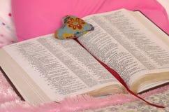 Otwiera biblię z faborkiem i sercem Zdjęcia Royalty Free