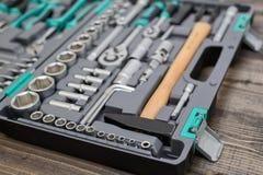 Otwiera czarnego toolbox z różnymi instrumentami na drewnianej powierzchni Obrazy Stock