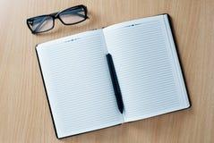 Otwiera dzienniczek z piórem i szkłami Fotografia Stock