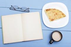 Otwiera książkę na drewnianym stole z białą stroną, filiżanki kawą z mlekiem i kulebiakiem, Nakreślenie dla kopia projekta lub pr obrazy stock