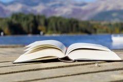 Otwiera książkę na Halnym jeziorze Obraz Royalty Free