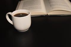 Otwiera książkę z filiżanką kawy przy czarnym stołem Obrazy Stock