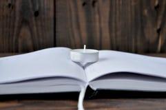 Otwiera ksi??k? lub notatnika Na książce jest mała świeczka zdjęcie royalty free