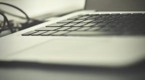 Otwiera laptop z akcesoriami smartphone i gadżet, na starym drewnianym biurku z pięknym światłem obraz stock