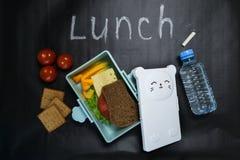 Otwiera lunchu pude?ko z kanapk? ca?y zbo?owy chleb, ser, zielona sa?atka, pomidor, og?rek i butelka woda na czerni, zdjęcie stock