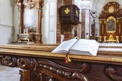 Otwiera modlitewną książkę na ławce w katedrze Obrazy Stock