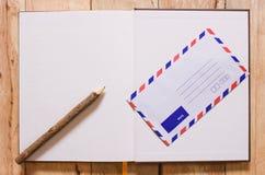 Otwiera notatnika i poczta na drewnianym tle kosmos kopii zdjęcie stock