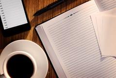 Otwiera notatnika z kawą przy telefon Obrazy Royalty Free