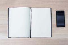 Otwiera notatnika z telefonem na drewnianym stole, odgórny widok Zdjęcie Stock