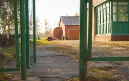 Otwiera ośniedziałe metal oficyny z cegła domem i bramę Zdjęcia Stock