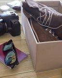 Otwiera pudełko z parą buty i kamera Mężczyzna przygotowywa przygoda fotografia royalty free