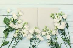 Otwiera pustego notatnika i bukiet białych kwiatów eustoma na błękitnym nieociosanym stołowym odgórnym widoku Kobiety pracujący b Obrazy Royalty Free