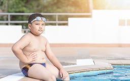 Otyły chłopiec obsiadanie w pływackim basenie Obrazy Stock