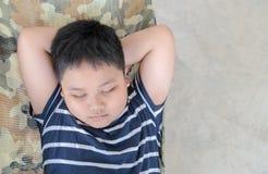 Otyły gruby chłopiec sen na kołysce w parku fotografia stock