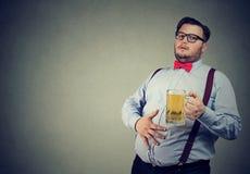 Otyły młody człowiek folujący z piwem obraz stock