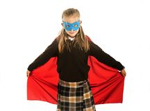 7 ou 8 années de jeune enfant féminin dans le costume de superhéros au-dessus de l'exécution d'uniforme scolaire heureuse et enth photo libre de droits