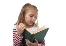 6 ou 7 anos pequenos doces novos velhos com a menina do cabelo louro que lê um livro que olha curioso e fascinado Foto de Stock