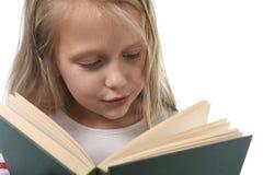 6 ou 7 anos pequenos doces novos velhos com a menina do cabelo louro que lê um livro que olha curioso e fascinado Imagens de Stock
