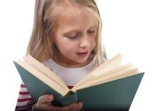 6 ou 7 anos pequenos doces novos velhos com a menina do cabelo louro que lê um livro que olha curioso e fascinado Imagem de Stock